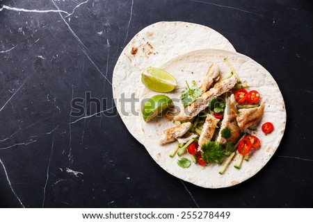 Tortillas filled with chicken and fresh vegetables on dark marble background - stock photo
