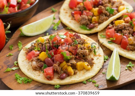 tortillas with chili con carne and tomato salsa on wooden board, horizontal