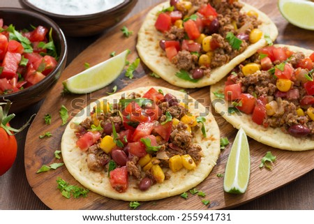 tortillas with chili con carne and tomato salsa on wooden board, top view, horizontal - stock photo