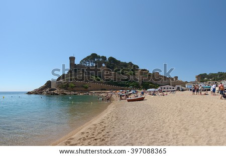 "TOSSA DE MAR, CATLONIA, SPAIN - JUNE 19: Resort vacationers are visiting Platja Gran beach near ""Vila Vella enceinte"" on June 19, 2014 in Tossa de Mar, Costa Brava, Catalonia, Spain."