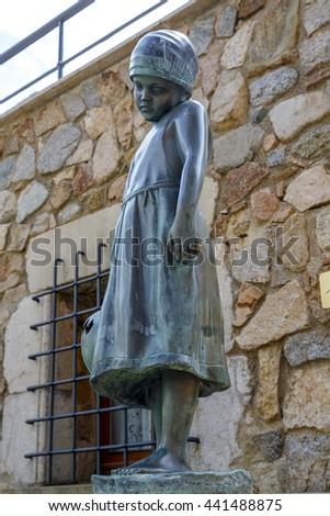 Tossa de Mar, Spain - May 31, 2015:  Lonely girl statue in old town street in Tossa de Mar (Costa Brava, Spain) - stock photo
