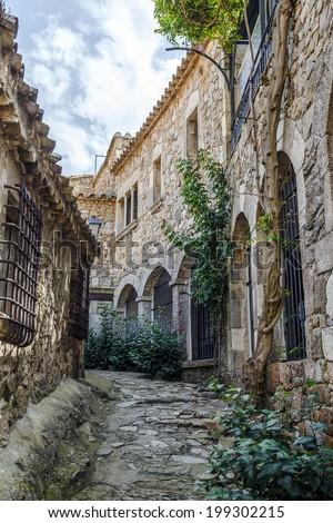 Tossa de Mar, Spain. Typical cobblestone streets of the city of fishermen - stock photo