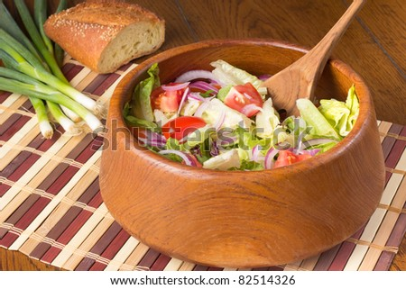 Tossed salad in a wooden bowl with green onions and bread in the background - stock photo