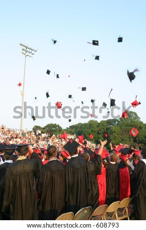 Tossing hats at a high school graduation. Vertical orientation. Editorial use only. - stock photo