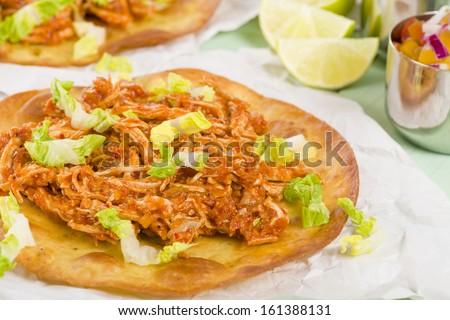 Tostadas - Mexican crispy corn tortilla topped with chicken tinga and lettuce. Served with pico de gallo, guacamole and crema mexicana. - stock photo