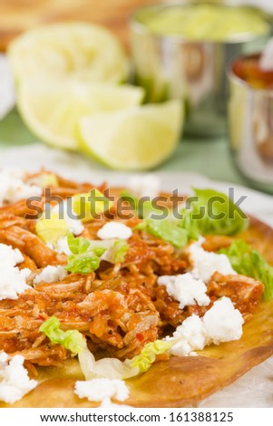 Tostadas - Mexican crispy corn tortilla topped with chicken tinga, lettuce and cotija cheese. Served with pico de gallo, guacamole and crema mexicana. - stock photo