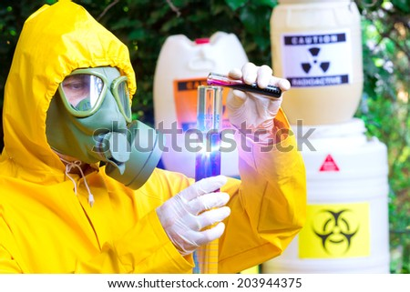 Total contamination ; Chemist in protective clothing with gas mask  examining toxic supsance,photography - stock photo