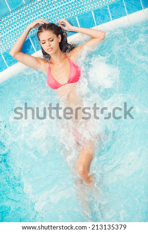 Total relaxation. Top view of attractive young woman in bikini relaxing in hot tub and keeping eyes closed - stock photo