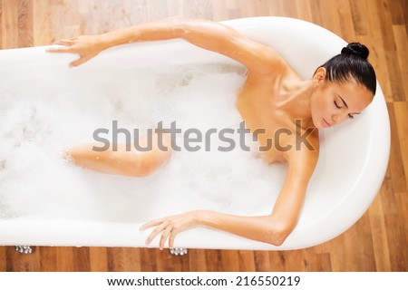 Total relaxation. Top view of attractive young woman keeping eyes closed while enjoying luxurious bath  - stock photo