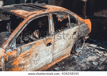 Totally incinerated burnt out luxury sedan in a scorched blacked paved courtyard, close up view through the shattered windows of the blackened interior of the vehicle - stock photo