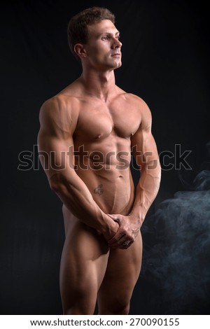Totally naked male bodybuilder hiding genitalia with hands, looking away, on dark background - stock photo