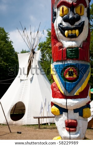 totem in front of indian tent