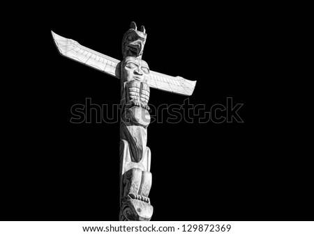 Totem pole on a  black background - stock photo