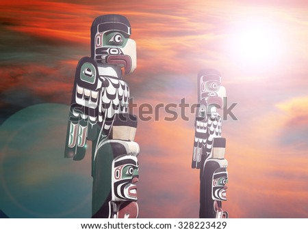 Totems in Courtenay with a sun and lens flare, Vancouver Island, Canada - stock photo