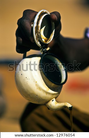Touareg hand pouring the tea in a camp - stock photo