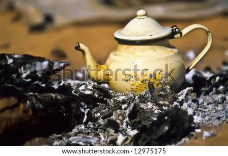 Touareg teapot on live coal in a camp - stock photo