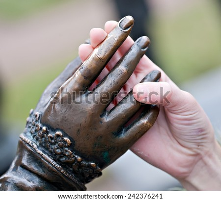 touch closeup of two hands: metal statue and human child - stock photo