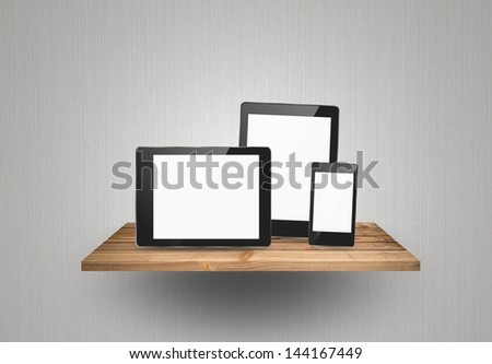 Touch screen device on wood shelf - stock photo