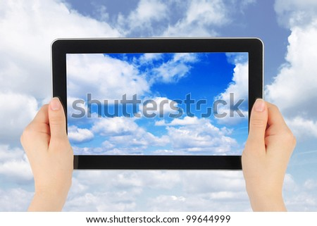 Touch screen device with blue sky in woman hands on blue sky background - stock photo