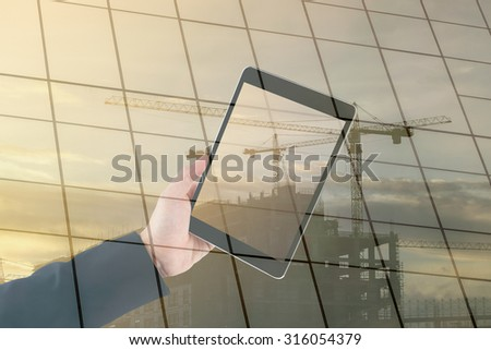 Touch screen tablet in hand on construction building background