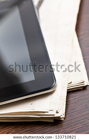 touch tablet and newspapers on wooden table - stock photo