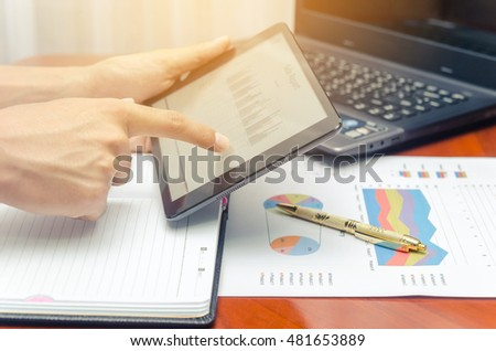 touch tablet working with black laptop and document chart on wood table