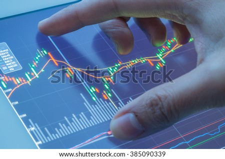 Touching stock market graph on a touch screen device. Close up shot. - stock photo