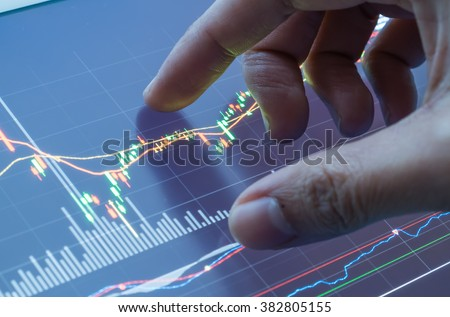 Touching stock market graph on a touch screen device. Closed up shot. - stock photo