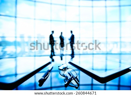Touchpads and glasses on table in boardroom - stock photo