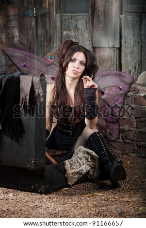 Tough fairy smokes cigarette in a rustic location - stock photo