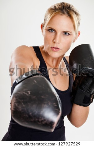 Tough female boxer punching wearing boxing gloves - stock photo