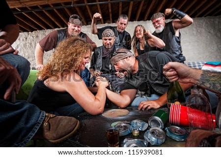 Tough female gang member winning arm wrestling match