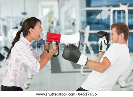Tough female trainer yelling to a man with a megaphone while boxing - stock photo
