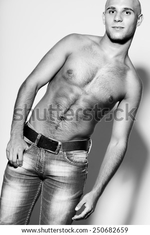 Tough guy concept. Beautiful (handsome) muscular male model with perfect body in trendy jeans with leather belt posing over gray background. Fashion studio black and white portrait - stock photo