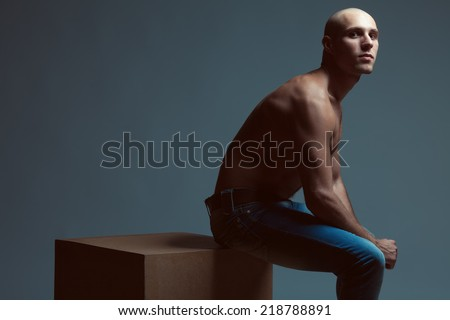 Tough guy concept. Handsome bald muscular male model in blue jeans with perfect muscular body posing over blue background, sitting on wooden cube. Vogue style. Copy-space. Fashion studio portrait - stock photo