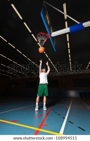 Tough healthy young man playing basketball in gym indoor. Wearing white shirt and green shorts. - stock photo