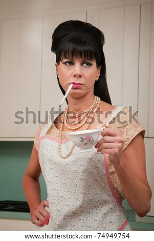 Tough housewife in apron with cigarette and coffee cup - stock photo