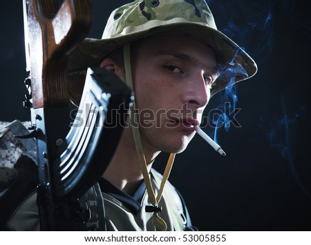 Tough looking soldier with Kalashnikov smoking cigarette.