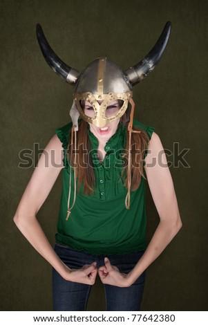 Tough-looking woman in Viking helmet flexes her biceps - stock photo