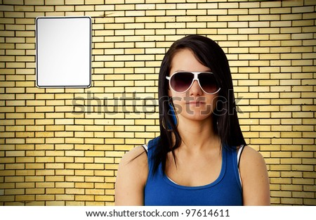 Tough looking young woman with sunglasses in front of yellow brick wall background with blank white metal sign ready for your text. - stock photo