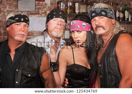 Tough male biker gang members with beautiful woman - stock photo
