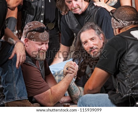 Tough male gang members in arm wrestling match