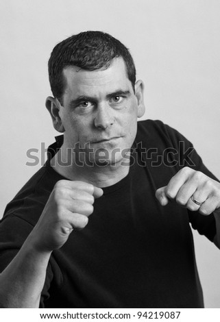 Tough man ready to fight boxing fists - stock photo