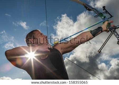 Tough man with bow and arrows, close up with cloudy sky at background. - stock photo