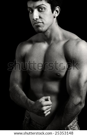 Tough muscular young man isolated on black background - stock photo
