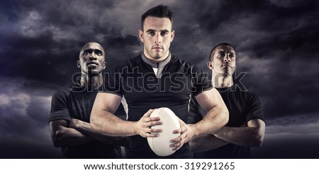 Tough rugby player looking at camera against blue sky - stock photo