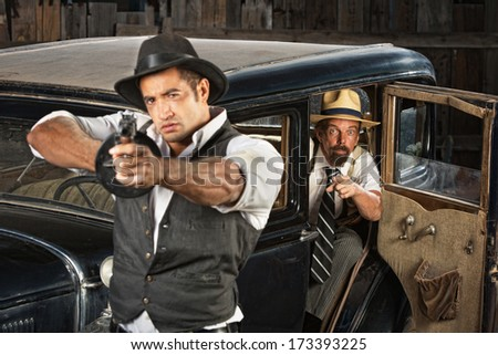 Tough 1920s vintage gangsters outside aiming guns from car - stock photo