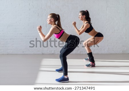 Tough stamina training for two young stunning fitness models doing squats together indoors. - stock photo