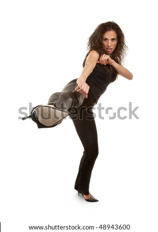 Tough woman in high heels kicking at camera - stock photo