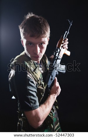 Tough young soldier in camouflage with Kalashnikov gun.